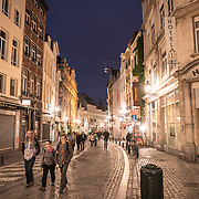 Tourists walking along a cobblestone street in the Lower Town of Brussels, Belgium, at night.