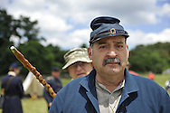Old Bethpage, New York, USA - July 21, 2012: GENE MONGELLO (front) of Levittown, is in Union uniform, and visitor PETER C. FALES of Bayshore, NY, behind him points his cane showing how a file closer soldier makes sure there are no empty places in a line file of soldiers during battle, at recreation of Camp Scott, a Union Army training camp, portrayed by Federal Re-enactors at Old Bethpage Village Restoration, to commemorate 150th Anniversary of American Civil War.