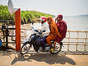 26 FEBRUARY 2015 - PHNOM PENH, CAMBODIA:   A motorcycle taxi takes a couple of Buddhist monks on a ferry crossing the Mekong River on the outskirts of Phnom Penh.  PHOTO BY JACK KURTZ