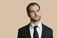 Young businessman looking away over colored background