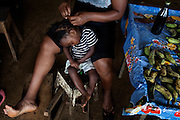 Sitting next to an open beer, a mother is tying her draught's braids in a small market area on the island of Principe, in Sao Tome and Principe, (STP) a former Portuguese colony in the Gulf of Guinea, West Africa.
