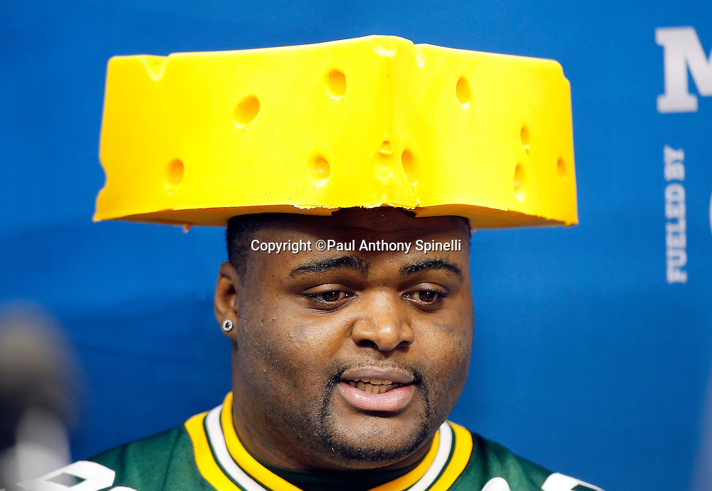 Green Bay Packers defensive tackle B.J. Raji (90) wears a cheese head hat as he speaks to the press at Super Bowl XLV media day prior to NFL Super Bowl XLV against the Pittsburgh Steelers. Media day was held on Tuesday, February 1, 2011 in Arlington, Texas. ©Paul Anthony Spinelli