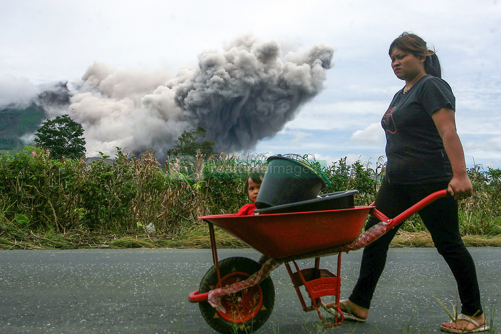 April 5, 2017 - A woman brings her daughter on wheelbarrow with background of Mount Sinabung volcano spewing smoke and ash at Beganding Village, Karo district, North Sumatra, Indonesia. The volcano has been put on highest level of alert since June 2015 following a significant increase of activity. (Credit Image: © Yt Haryono/Xinhua via ZUMA Wire)