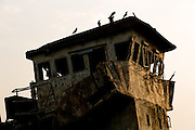 Rusted ship cabin with birds on roof, YangonYangon