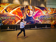 20 NOVEMBER 2014 - BANGKOK, THAILAND: A woman walks past a poster for the new Hunger Games movie at Siam Paragon theaters in Bangkok. At least three people were arrested by Thai police during the opening the Hunger Games: Mockingjay - Part 1 in Bangkok Thursday. Opponents of the Thai military coup have adapted the three fingered salute used in the Hunger Games series as a sign of their opposition to the coup. In the weeks before the movie opening Thai police arrested several people for using the Hunger Games salute and Thai media reported that one Thai movie theater chain cancelled plans to show the movie at the request of the military government. There were several small protests at theaters showing the movie Thursday.     PHOTO BY JACK KURTZ