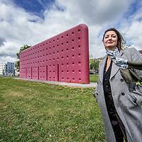 Nederland, Amsterdam, 15 mei 2016.<br /> Esther Eikelenboom over het kunstwerk De Muur van haar vader Alfred Eikelenboom (1936-2014).<br /> Het kunstwerk staat op een grasveldje tussen de Meeuwenlaan en de Gedempte Insteekhaven in Noord. Het is een grote rode muur.<br /> <br /> <br /> Foto: Jean-Pierre Jans