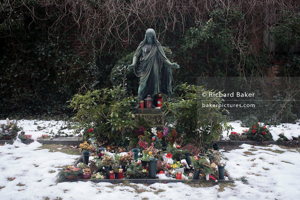 A Jesus statue looks down on a shrine for an unknown person in a cemetery in Wedding, a north-western district of Berlin.
