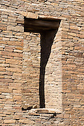 Stone doorway. Pueblo Bonito is a monumental public building (Puebloan Great House) occupied from around 828 to 1126 AD, now preserved at Chaco Culture National Historical Park, New Mexico, USA. The huge D-shaped complex of Pueblo Bonito enclosed two plazas with dozens of ceremonial kivas, plus 600 rooms towering 4 and 5 stories above the valley floor. The functions of this building included ceremony, administration, trading, storage, hospitality, communications, astronomy, and burial, but few living quarters. Chaco Culture NHP hosts the densest and most exceptional concentration of pueblos in the American Southwest and is a UNESCO World Heritage Site, located in remote northwestern New Mexico, between Albuquerque and Farmington. From 850 AD to 1250 AD, Chaco Canyon advanced then declined as a major center of culture for the Ancient Pueblo Peoples. Chacoans quarried sandstone blocks and hauled timber from great distances, assembling fifteen major complexes that remained the largest buildings in North America until the 1800s. Climate change may have led to its abandonment, beginning with a 50-year drought starting in 1130.