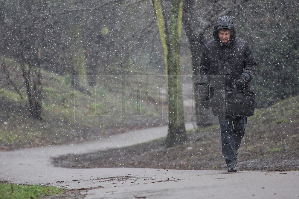 © licensed to London News Pictures. London, UK 23/03/2013. People walking under snow and rain in Battersea Park, London on Saturday, 23 March 2013. Photo credit: Tolga Akmen/LNP