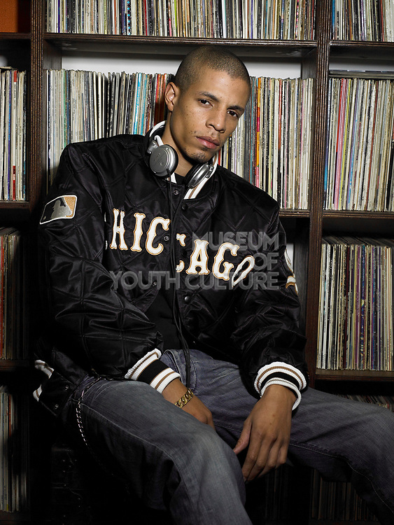 Young man wearing headphones around neck sat leaning against shelves of vinyl records.