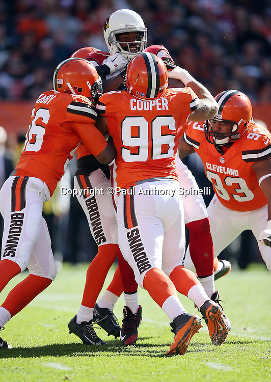 Arizona Cardinals tight end Jermaine Gresham (84) catches a first quarter pass for a gain of 6 yards and a first down at the Cleveland Browns 16 yard line as he gets gang tackled from all sides by Cleveland Browns inside linebacker Karlos Dansby (56), Cleveland Browns defensive tackle Xavier Cooper (96), Cleveland Browns defensive end John Hughes (93), and another Browns teammate during the 2015 week 8 regular season NFL football game against the Arizona Cardinals on Sunday, Nov. 1, 2015 in Cleveland. The Cardinals won the game 34-20. (©Paul Anthony Spinelli)