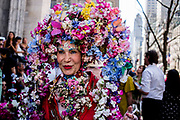 New York, NY - April 16, 2017. A woman wears an elaborate arched headpiece covered with hundreds of flowers at New York's annual Easter Bonnet Parade and Festival on Fifth Avenue.
