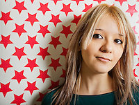 Close-up of beautiful young woman against red star shapes wallpaper