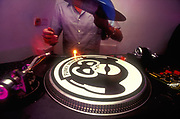 A DJ about to put a record on the decks with a 'Funky Monkey' slipmat