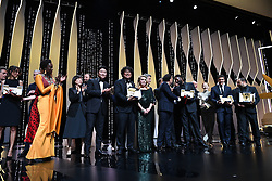 """South Korean director Bong Joon-Ho (3rdL) poses on stage with the Palme d'Or award he received for the film """"Parasite (Gisaengchung)"""" as (FromL) a translator, South Korean actor Song Kang-ho, US director and member of the jury of the Cannes Film Festival Kelly Reichardt, French actress Catherine Deneuve, Polish director and member of the jury of the Cannes Film Festival Pawel Pawlikowski, Mexican director and President of the Jury of the Cannes Film Festival Alejandro Gonzalez Inarritu, French director and member of the jury of the Cannes Film Festival Enki Bilal, French director Ladj Ly, holding his Jury Prize for """"Les Miserables"""" and British actress Emily Beecham, holding her Best Actress prize for """"Little Joe"""" join him on stage on May 25, 2019 at the end of the closing ceremony of the 72nd edition of the Cannes Film Festival in Cannes, southern France. Photo by David Niviere/ABACAPRESS.COM"""