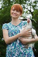 Woman holding hen in garden portrait