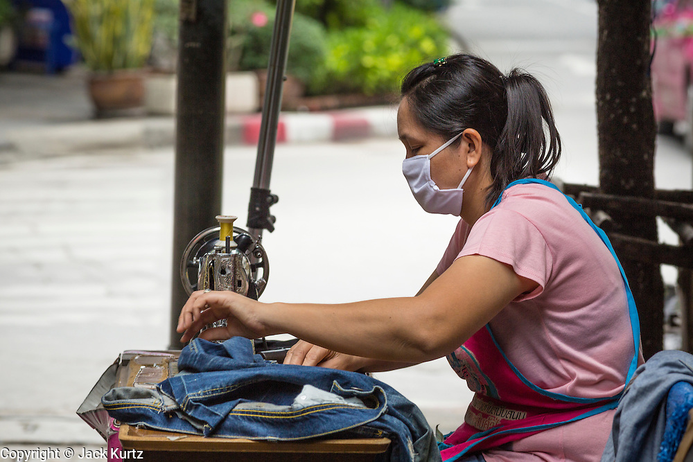 "24 AUGUST 2013 - BANGKOK, THAILAND: A seamstress works on a street in Bangkok. Workers in the informal economy have not been impacted by the recession yet but more and more people are joining the informal economy. Thailand entered a ""technical"" recession this month after the economy shrank by 0.3% in the second quarter of the year. The 0.3% contraction in gross domestic product between April and June followed a previous fall of 1.7% during the first quarter of 2013. The contraction is being blamed on a drop in demand for exports, a drop in domestic demand and a loss of consumer confidence. At the same time, the value of the Thai Baht against the US Dollar has dropped significantly, from a high of about 28Baht to $1 in April to 32THB to 1USD in August.     PHOTO BY JACK KURTZ"