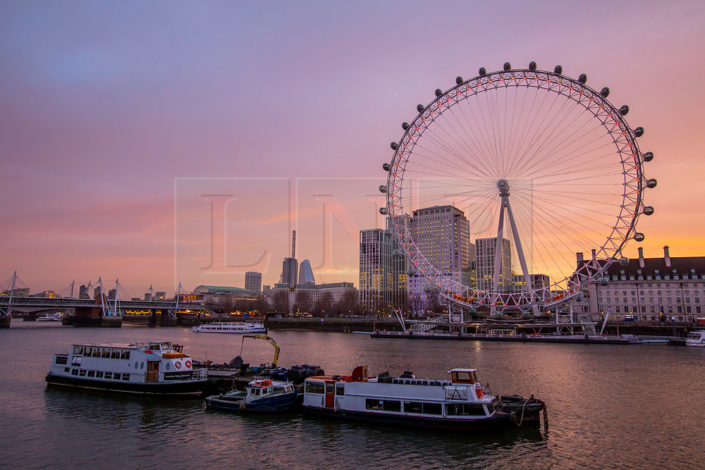 © Licensed to London News Pictures. 10/12/2019. London, UK. Commuters were greeted with pink and orange skies this morning as the sun rises over the London Eye and Southbank. Weather experts predict wind, rain and showers developing later which will continue for the General Election on Thursday 12th December 2019. Photo credit: Alex Lentati/LNP