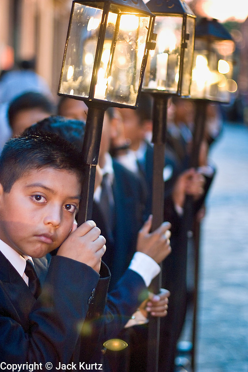 09 APRIL 2004 - SAN MIGUEL DE ALLENDE, GUANAJUATO, MEXICO: Boys, all dressed in black, form the Good Friday procession from Iglesia Oratorio in San Miguel de Allende, GTO, MEX. The Good Friday procession from Oratorio is one of the most ornate in Mexico. The dignitaries, whose role in the procession is handed down from father to son and mother to daughter, accompany the procession carrying tall lantern and statues representing aspects of the life of Christ. Semana Santa, the week before Easter, is celebrated with extreme piety in central Mexico. San Miguel, which was founded in the 1600s, is one of Mexico's premier colonial cities. It has very strict zoning and building codes meant to preserve the historic nature of the city center. About 7,500 US citizens, mostly retirees, live in San Miguel. PHOTO BY JACK KURTZ