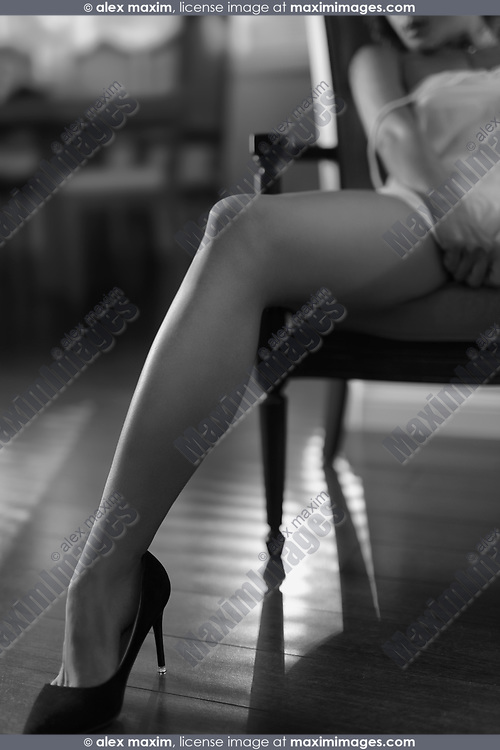 Sexy long legs in high heel shoes, sensual black and white closeup of a woman sitting in a chair wearing a night shirt