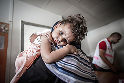 © Licensed to London News Pictures. 21/07/2014. Gaza. A young girl waiting with her mother to recieve treatment. Refugees including women and children caught in the conflict between Israel and Hamas receive medical treatment at a UN school being used as a hospital on the edge of the Jabalaya district of Gaza. The health of Children is suffering with some not eating and sleeping as a result of the conflict. Skin conditions, infection and gastro problems are increasing amongst the young.   As the Israel/Gaza conflict intensifies the number of displaced people has now risen to over 47,000 (Source - UNRWA). Photo credit : Alison Baskerville/LNP