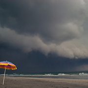 An beach umbrella stands abandoned in front of an oncoming thunderstorm on Wrightsville Beach, NC. .