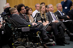 © London News Pictures. 30/04/2013. London, UK. Professor Stephen Hawking (left) at the launch of a report by the charity Breathe On UK at Portcullis House in London on April 30, 2013. Breathe On UK supports families of children on long-term ventilation. Photo credit: Ben Cawthra/LNP.