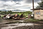 School girls weave their way through scrap metal waiting to be sold in Panama City, Boca de Sabalo, Darien Province, Panama.