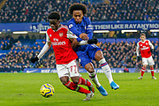 Chelsea midfielder Willian (10) battles for possession with Arsenal midfielder Bukayo Saka (77) during the Premier League match between Chelsea and Arsenal at Stamford Bridge, London, England on 21 January 2020.