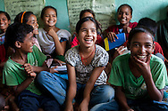 Sarawati Regmi (white), 11, attends a club meeting at the Kishuri Sachetana Child Club in their activity center in Thahuri Tole, Chhinchu, Surkhet district, Western Nepal, on 1st July 2012. Sarawati's ambition is to run an NGO. 16-year-old Bhawani Regmi (in grey/pink) who is the president of the district level child forum, 11-year-old  Sarawati Regmi (in white), and 10-year-old Ganga Regmi (in pink) are daughters of pandit (Hindu priest) Dharma Raj Regmi who is one of the 3 priests who have agreed to stop solemnizing child marriages. These Child Clubs, supported by the government, Save the Children and their local partner NGO Safer Society, advocate for child rights and against child marriages and use peer support and education to end child marriages and raise awareness. Photo by Suzanne Lee for Save The Children UK