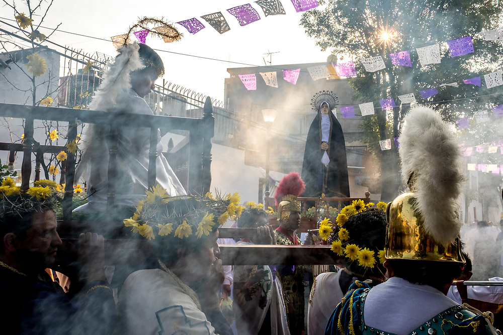 Catholic devotees carry a statue of the Vrigin Mary through the streets of Iztapalapa, clouded in incese smoke.