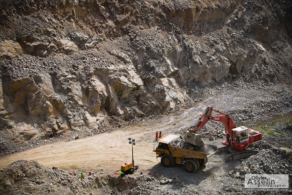 An excavator loads a large truck with ore in a pit of the Youga gold mine near the town of Youga, approximately 205 km southeast of Burkina Faso's capital Ouagadougou on Tuesday April 28, 2009..