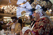 A carnival character in costume in caffè Lavena in Venice during the carnival.