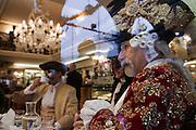 A carnival character in costume in caffè Lavena in Venice during the carnival.