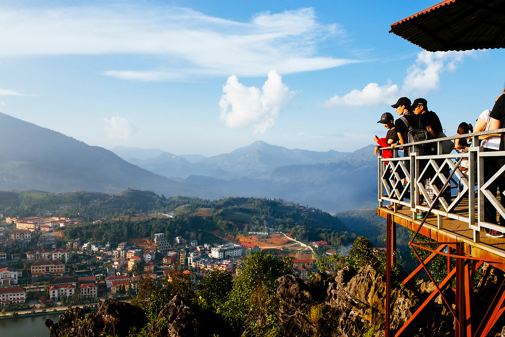 Travelers overlook a mountainous landscape in Sapa, Vietnam.