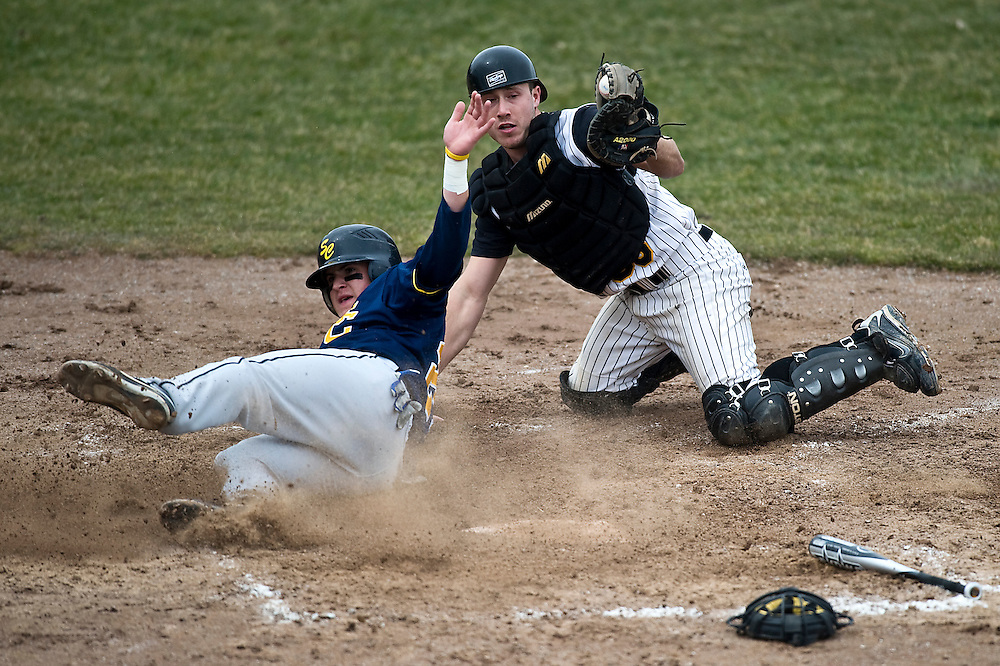 Matt Dixon | The Flint Journal..Mott Catcher Jake Bourassa holds on to the ball after tagging out a St. Clair runner in the second inning in Mott's conference home-opener at Broome Park in Flint Friday afternoon.Mott defeated St. Clair 6 to 5 in the bottom of the eighth inning.