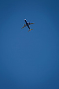 An Airbus 737-320 jet airliner (G-EUYH) with British Airways flies overhead in blue skies on its flight-path into London Heathrow airport, on 8th August 2018, in London, England.