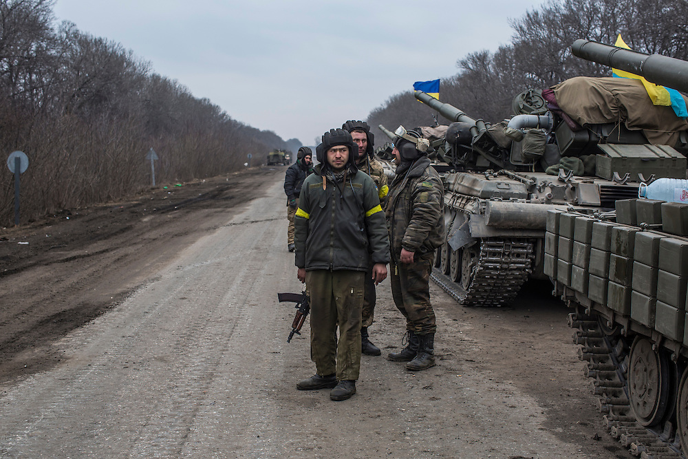 ARTEMIVSK, UKRAINE - FEBRUARY 19: Ukrainian soldiers stand with their tanks on a roadside leading out of Debaltseve on February 19, 2015 in Artemivsk, Ukraine. Ukrainian forces have begun withdrawing from the strategic and hard-fought town of Debaltseve after being effectively surrounded by pro-Russian rebels. (Photo by Brendan Hoffman/Getty Images) *** Local Caption ***