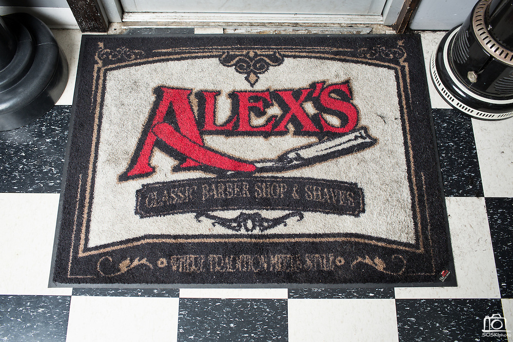A weathered welcome mat see the soles of more than 60 visitors a day at Alex's Classic Barber Shop & Shaves in Fremont, California, on April 9, 2014. (Stan Olszewski/SOSKIphoto)
