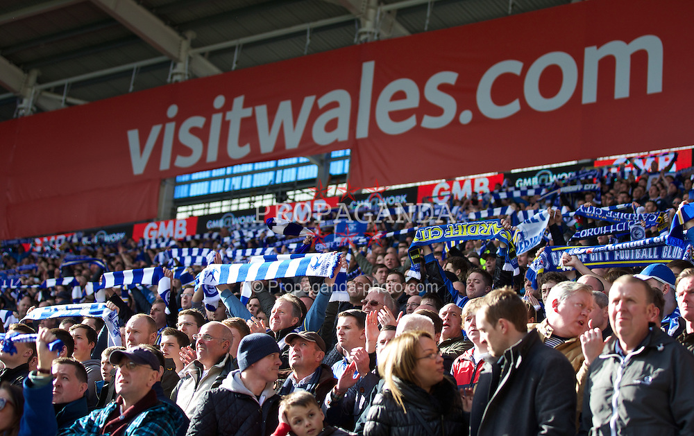 CARDIFF, WALES - Saturday, March 22, 2014: Cardiff City supporters hold aloft blue scarves as they protest against the Chairman who changed their home kit from blue to red, during the Premiership match at the Cardiff City Stadium. (Pic by David Rawcliffe/Propaganda)