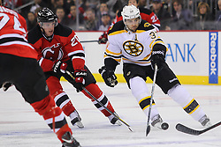 Jan 4, 2012; Newark, NJ, USA; Boston Bruins center Patrice Bergeron (37) skates with the puck while being defended by New Jersey Devils center Ryan Carter (20) during the first period at the Prudential Center.