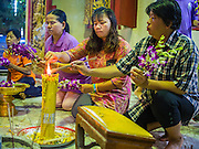 """07 MARCH 2015 - NAKHON CHAI SI, NAKHON PATHOM, THAILAND: Women pray in a chapel at the Wat Bang Phra tattoo festival. Wat Bang Phra is the best known """"Sak Yant"""" tattoo temple in Thailand. It's located in Nakhon Pathom province, about 40 miles from Bangkok. The tattoos are given with hollow stainless steel needles and are thought to possess magical powers of protection. The tattoos, which are given by Buddhist monks, are popular with soldiers, policeman and gangsters, people who generally live in harm's way. The tattoo must be activated to remain powerful and the annual Wai Khru Ceremony (tattoo festival) at the temple draws thousands of devotees who come to the temple to activate or renew the tattoos. People go into trance like states and then assume the personality of their tattoo, so people with tiger tattoos assume the personality of a tiger, people with monkey tattoos take on the personality of a monkey and so on. In recent years the tattoo festival has become popular with tourists who make the trip to Nakorn Pathom province to see a side of """"exotic"""" Thailand.   PHOTO BY JACK KURTZ"""