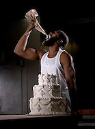African American man with a wedding cake and eating icing.