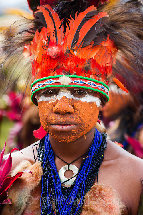 Young man with his face painted orange and white, wearing a traditional red feather headdress and a blue necklace of seashells. Goroka Festival in the highlands of Papua New Guinea.