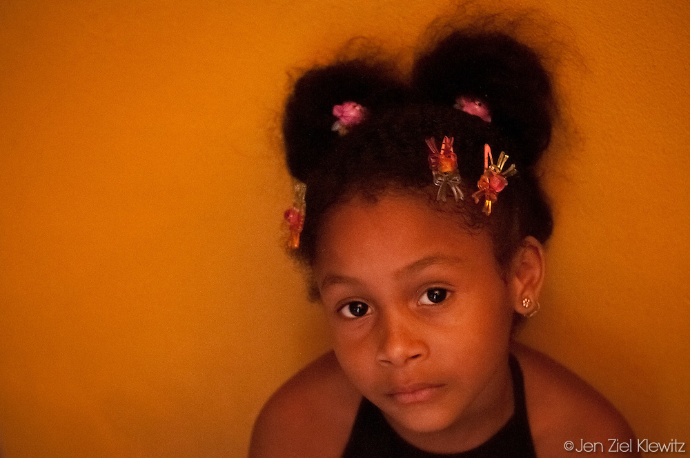 Stefanie Pelegrino, 7, of the Habana, Cuba neighborhood of Jesus Maria, sits for a portrait. Photo by Jen Klewitz