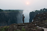 Obino Simwaba looks towards Zimbabwe from the lip of Victoria Falls at sunset. Obino has been a guide at the park from seven years.