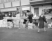 Moore Street, Dublin.      (J97)..1975..23.12.1975..12.23.1975..23rd December 1975..For well over a hundred years Moore Street has served the citizens of Dublin. The longest running open air fruit and vegatable market offers value for money,particularly to those where money is in short supply. Predominately a fruit and veg market there are several traders who sell fish and seasonal goods, as illustrated by the photographs showing turkeys and holly wreaths being sold on the run up to Christmas..Image shows produce stacked behind the stall as the trader weighs fruit for a customer.