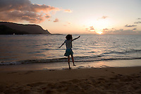 A girl dances on the beach at sunset at the Princeville Resort, Kauai, Hawaii
