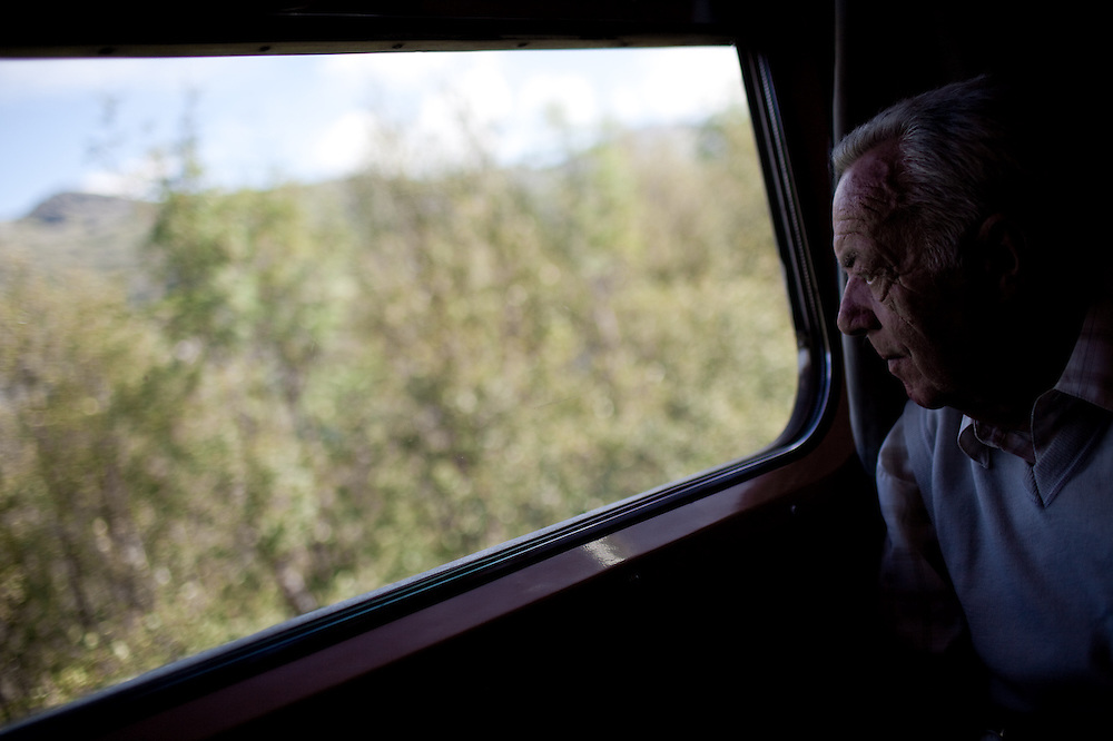 A passenger on the Flåm Railway, one of the steepest in the world, gazes down at the city of Flåm in the valley below, Norway.