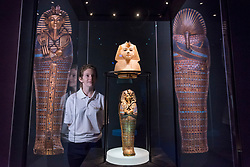 "© Licensed to London News Pictures. 01/11/2019. LONDON, UK. A staff member views ""Calcite Stopper for Canopic Jar, King's Head: NW"" and ""Gold Inlaid Canopic Coffinette of Tutankhamun Dedicated to Imseti and Isis"".  Preview of ""Tutankhamun, Treasures of the Golden Pharoah"" at the Saatchi Gallery in Chelsea.  The exhibition celebrates the 100th year anniversary of the opening of Tutankhamun's tomb and displays 150 works in the largest collection of Tutankhamun's treasures ever to leave Egypt.  The show runs 2 November to 3 May 2020.  Photo credit: Stephen Chung/LNP"